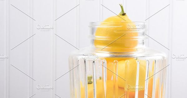 Glass jar full of fresh picked whole lemons. An old fashioned juicer is on the table next to the jar. Vertical with copy space.