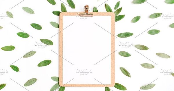 Clipboard with green petals on white background.