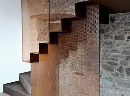 Beautiful iron staircase contrasting the stone wall.
