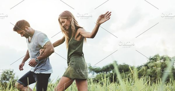 Outdoor shot of young couple walking through meadow hand in hand. Man and woman talking walk through grass field in countryside.