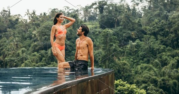 Outdoor shot of happy young couple relaxing at edge of swimming pool. Man and woman enjoying holiday at luxury resort in nature.