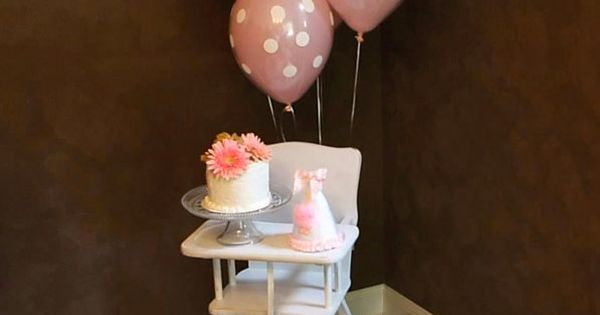 Birthday party ideas - Balloons behind high chair for cute photos.