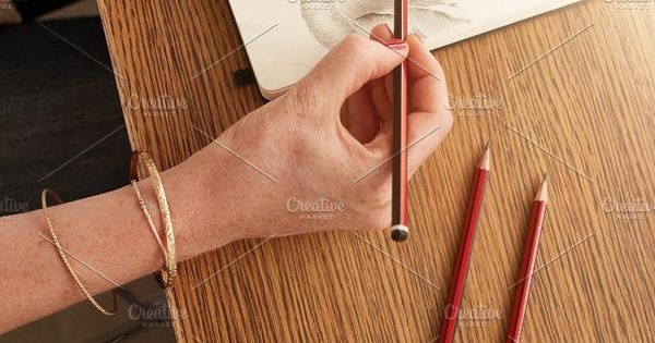 Woman sitting at a table sketching a flower on art book. Top view of female hands making a floral sketch.
