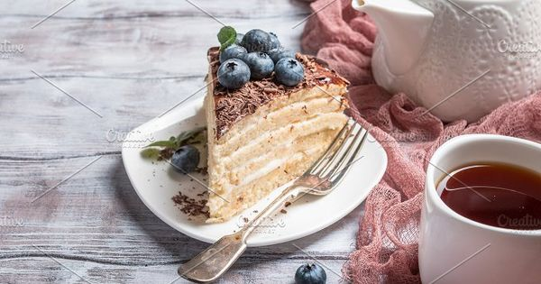 Piece of delicious sponge cake with cream and chocolate on plate