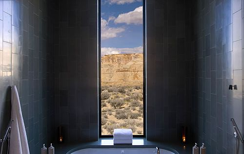 A dark grey, fully tiled bathroom with stunning views from a window