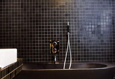 Black bathtub, black tile, black bathroom