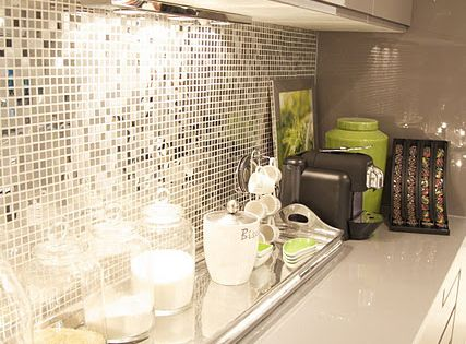 Glossy white counters, white cabinetry with under cabinet lighting, disco inspired glass