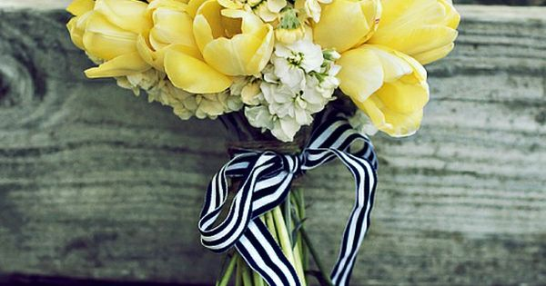 Yellow tulips are combined with bright yellow billy balls, creme and butter