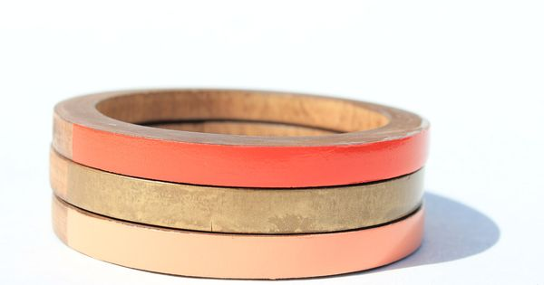 Skinny stacked bangles in gold, peach, and red.