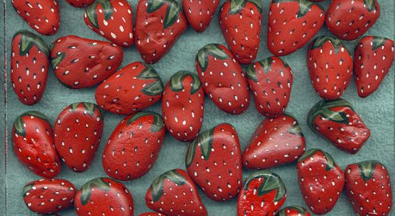 """Stones painted as strawberries when put around strawberry plants in the spring"