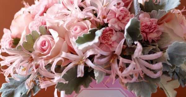 The vase underneath this bunch of roses, dusty miller foliage, and nerine lilies is wrapped to look like a box of chocolate.