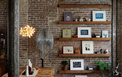 buttresses. Loft. Exposed brick wall. Simple wooden table. Floating shelving against wall.