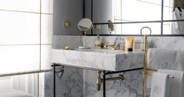 gold fixtures in bathroom contrast the black & white of marble, pendant