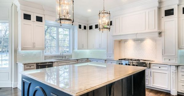 A pair of glass and nickel lanterns hang over a black - Kitchen island decorative trim ...