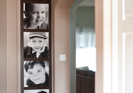pictures stacked vertically at end of hallway to look like photo booth