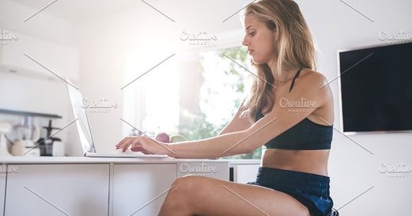 Side view of young woman using laptop computer in the kitchen. Caucasian female working on laptop in morning.