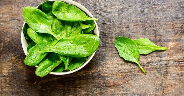 Fresh green spinach in bowl on rustic wooden background