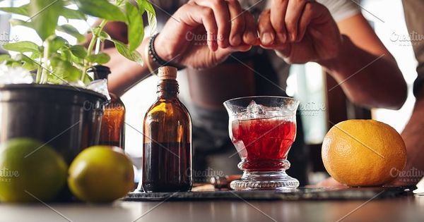 Close up shot of bartender hands preparing negroni cocktail with grapefruit. He is putting some essence from grapefruit skin into the cocktail glass on counter.