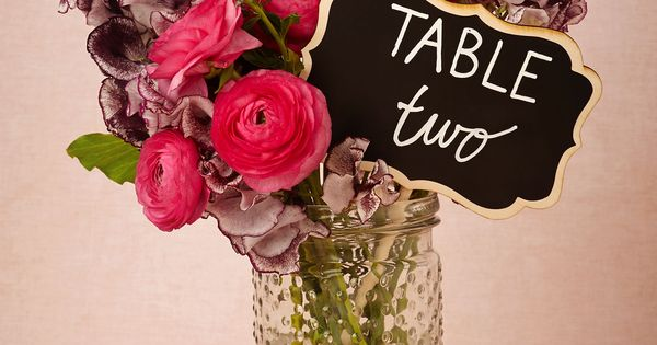 Table signs in flower arrangement vase....  Hobnail Glass Jars in DA�cor Centerpieces at BHLDN