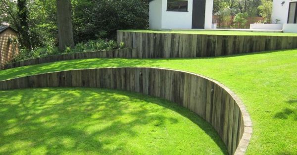 Curved timber retaining wall with vertical railway sleepers, great against a lawn.