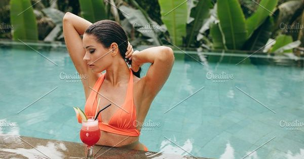 Portrait of attractive young woman in swimming pool with cocktail . Caucasian female standing in the pool.