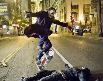 Heath Ledger as the Joker skate boarding over Christian Bale as Batman