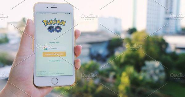 Hand holding Apple iPhone6s showing sign up screen of Pokemon Go application