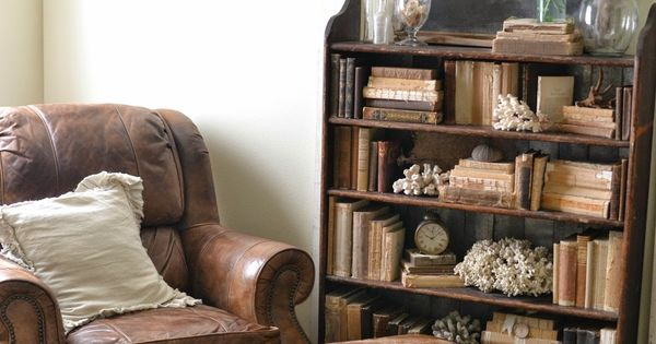 Faded Charm... worn leather chair and ottoman... bookcase with worn vintage books...