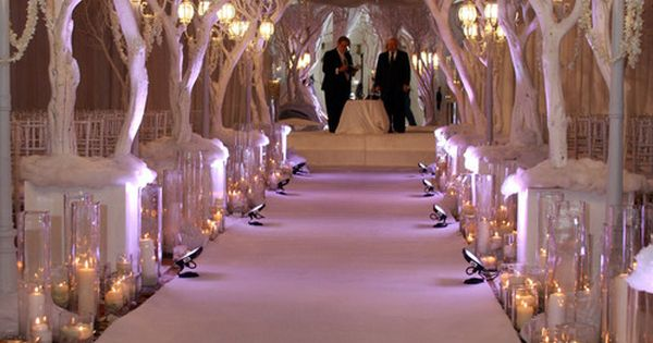Winter wonderland wedding aisle with white trees and candles.