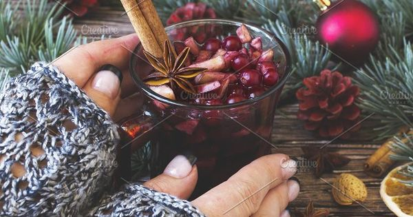woman's hands holding a cup of mulled wine between Christmas balls with fir branches lying on a wooden table, selective focus