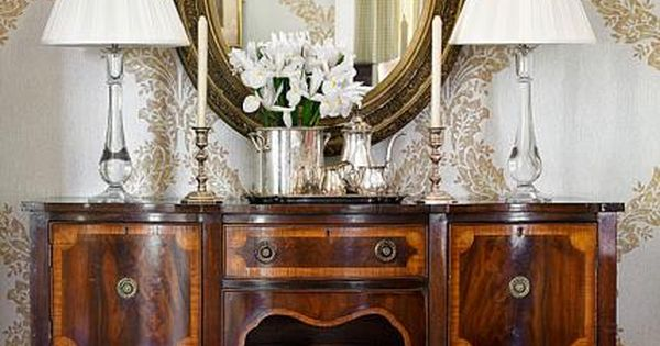 antique sideboard and oval mirror pump up the glam in this dining room