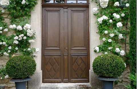 white roses around front door. PRETTY! The door should be a glossy