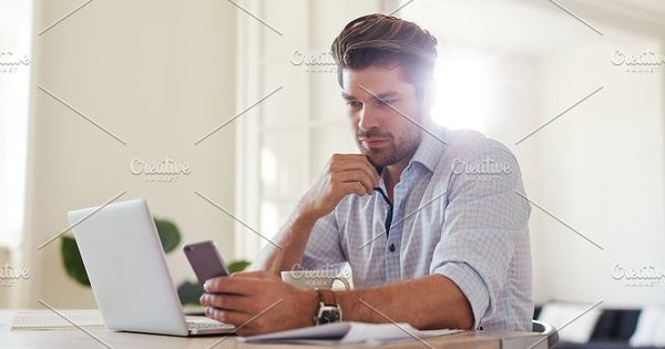 Indoor shot of young man reading text message on mobile phone while sitting at table at home. Business man at home office with smart phone and laptop.