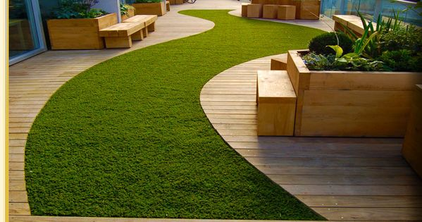 synthetic lawn and curved timber deck looks lovely and well manicured. deck