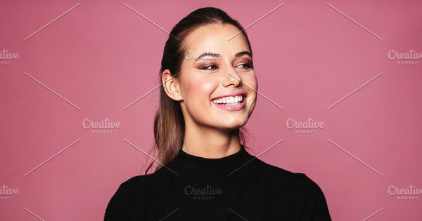 Portrait of caucasian female model standing and smiling against pink background. Beautiful woman with perfect skin and makeup looking away.