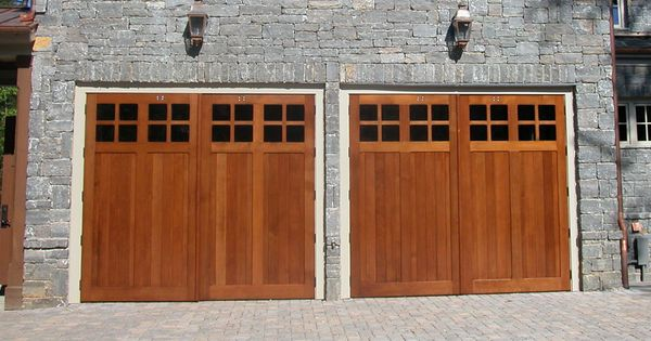 Carriage house garage doors against stone veneer nice for Wood veneer garage doors