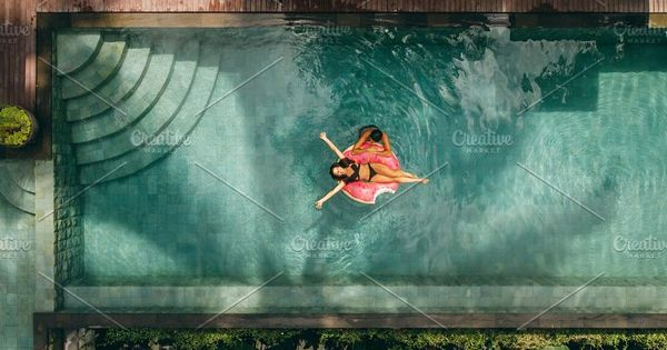 Aerial view of couple enjoying in resort pool. Young woman lying on inflatable ring with man in resort swimming pool.