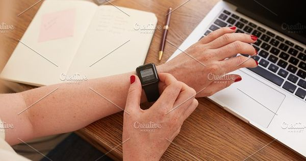 Close up of smartwatch on woman's hand, she is using the smart wrist watch while sitting at her work desk.
