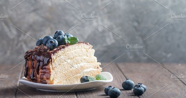side view of a piece of delicious sponge cake with cream and chocolate on plate