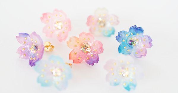 七色の桜をそれぞれのイメージで描いてみました 一つの花の中に鮮やかに色が混ざり合っています 中央にはスワロフスキークリスタルを置きその周りのブリオンを配置しました ホログラムの細かなラメが反射して繊細でキラキラきれいです お色のご注文方法 ご注文の