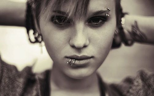 Paired lower lip piercings and double eyebrow piercings