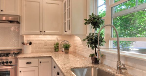 Giallo Ornamental Granite, beveled white subway tile back splash and white cabinets.