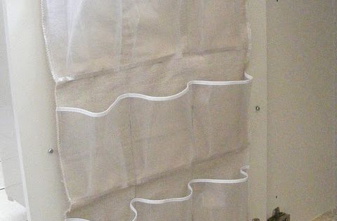 Attach half of a shoe organizer to the inside of a bathroom
