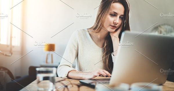 Attractive young woman using laptop while working at home interior, casual style, long hours at work, pretty female student using portable computer at coffee shop