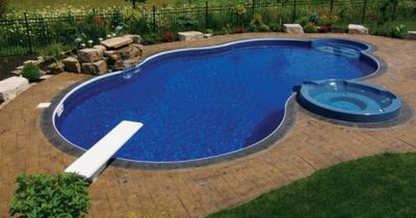 Inground Pools With Diving Board And Slide freeform swimming pool with water wall, slide, diving board, and