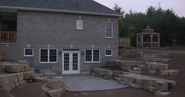 Walkout Basement With Limestone Tiered Retaining Walls This Is Similar To How The West Side Of Exterior Stairs Concrete Retaining Walls Walkout Basement Patio