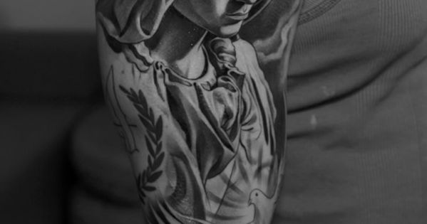 Elegant tattoo by Jun Cha of Mary & Jesus. This tattoo is