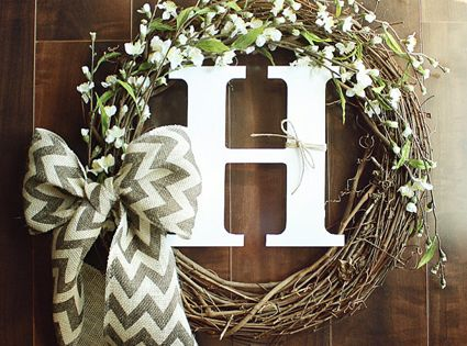 Monogrammed Grapevine Wreath with white flower details intertwined a Chevron Burlap Bow-