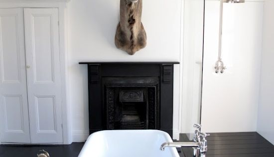 black and white bathroom, clawfoot tub, animal head, wooden stool.