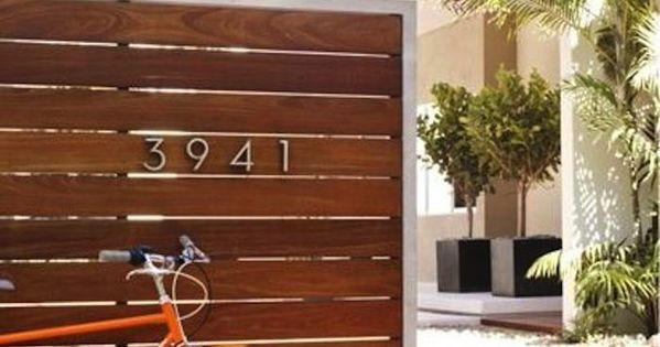 Slatted wooden fence, aluminum Neutra House Numbers & a fabulous orange bike.